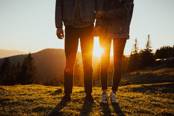 Legs of travelers at sunset near mountain.Couple holding hands.Cropped image of two hikers legs standing on a peak and looking at the view.