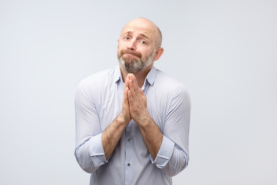 Please help me now. Bearded mature man need a help. Isolated on gray background, studio shot