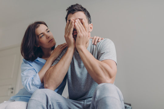 Photo of depressed male dressed casually, his beautiful woman comforts him, sit together in bedroom, have problems in family life. Affectionate wife consoles husband in difficult situation.