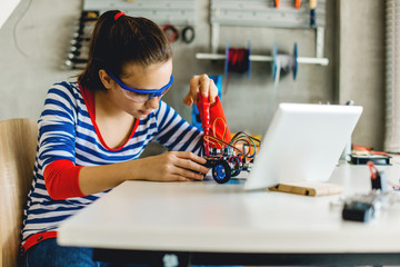 Young girl fixing mechanical car toy