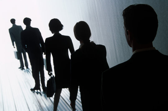 A line of people, men and women in silhouette, walking towards a very bright light, following a set path, following, waiting.