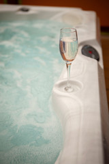 Glass of bubbly sitting on the side of a hot tub