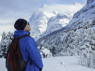 close-up portrait of a tourist looking up at the winter slopes of the mountains, Swiss Alps