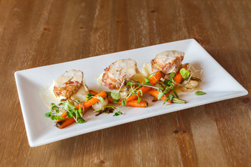 Chicken on a white plate, served with carrots and greens