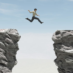 Young man jumping over the chasm.