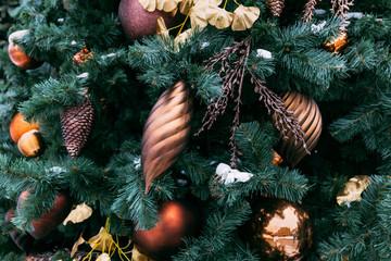 Christmas tree closeup. Golden balls and illuminated garland with flashlights.