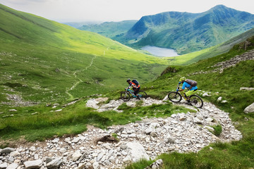 Mountain Bikers descending fast towards a long trail and lake in the Lake District