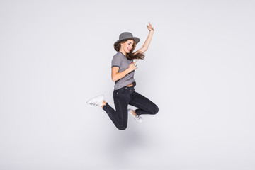 Full length portrait of satisfied american woman wearing jeans and t-shirt jumping isolated over white background