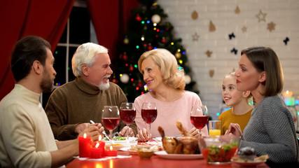 Happy family having tasty Christmas dinner together, lights on tree glittering