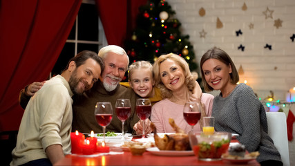 Big family hugging, smiling and looking to camera at Christmas dinner, portrait