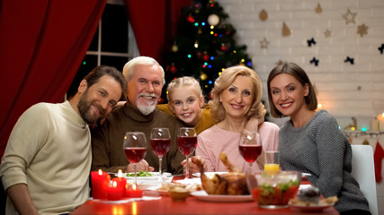 Friendly family hugging and looking into camera, Xmas dinner traditions