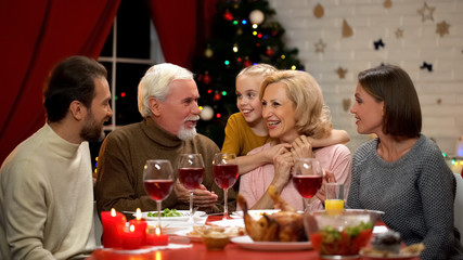 Happy family chatting at Xmas dinner telling funny stories, girl hugging granny