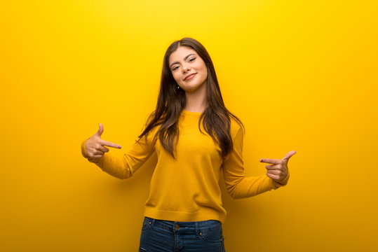 Teenager girl on vibrant yellow background proud and self-satisfied in love yourself concept