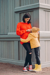 Photo of happy young mum touches nose of her curious pleased daughter, stand closely to each other at corner of wooden building. Lovely small child wears hat, jacket and boots, has fun with mother