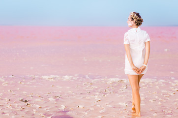 Pink salt lake and younf woman in white