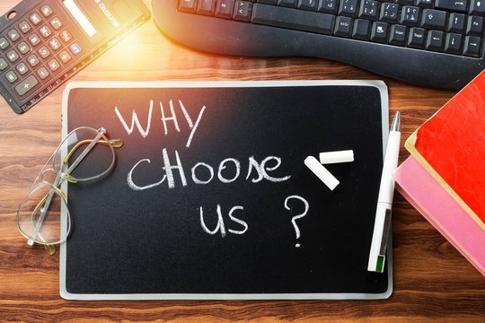 why choose us ? question writing with white chalk on blackboard and keyboard, books and calculator, eyeglasses