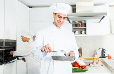 Smiling male kitchener in uniform is standing with pan in the kitchen