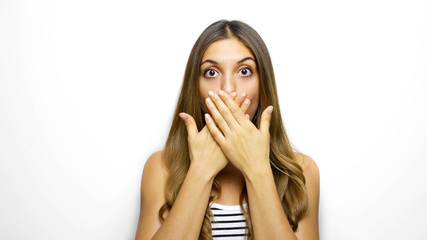 Pretty girl covering her mouth over white background