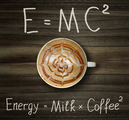 The cup of black coffee with milk and two formulas. E = mc2. Wood background.
