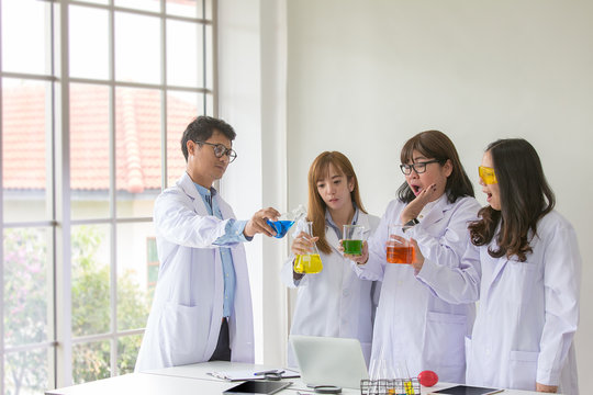 Science Test. Chemist scientific testing quality. Group Scientist working at laboratory. One Man and Three woman at chemistry lab. Asian people. Life scientist researching in laboratory