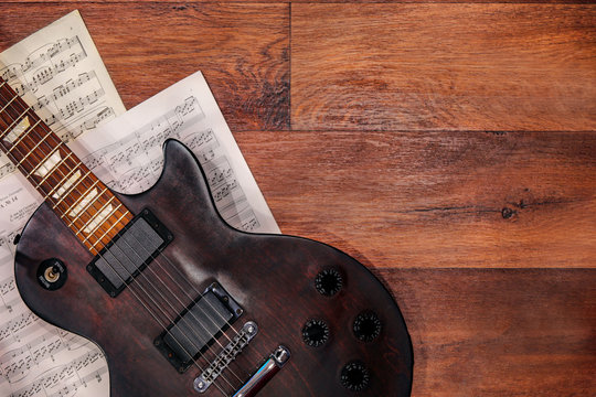 guitar and sheet music on wooden background, electric guitar flat lay