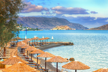 Panoramic view of the gulf of Elounda with the famous village of Elounda and the island of Spinalonga at sunset with nice clouds and calm sea, Crete, Greece.