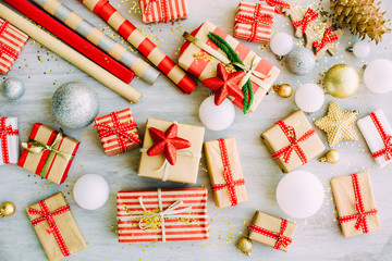 Christmas background with confetti, christmas balls, and red gift boxes on the white wooden board