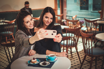 Beaufitul smiling girlfriends taking selfie