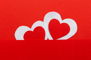 Valentines day. Paper hearts red and white on a red background. Holiday background