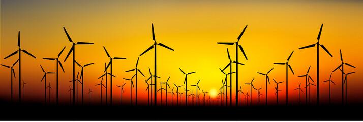 Wind power turbine silhouettes on sunset background