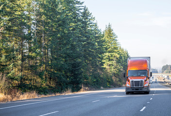 Front view of big rig orange semi truck with semi trailer driving up the hill on wide multiline highway