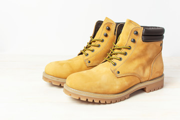Yellow men's work boots from natural nubuck leather on wooden white background. Trendy casual shoes, youth style. Concept of advertising autumn winter shoes, sale, shop.