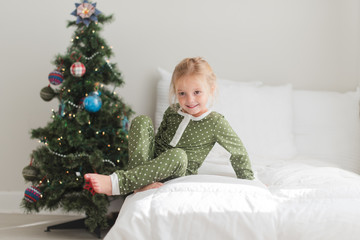 Young girl sitting on bed nearby a Christmas tree