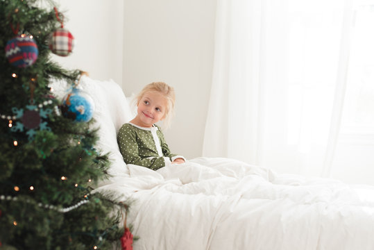 Young girl sitting in bed looking at Christmas tree