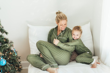 Mother and daughter sitting on a bed next to a Christmas tree