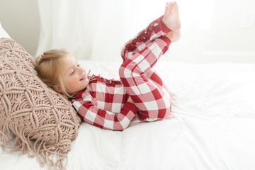 Smiling young girl in pajamas lying down on a bed