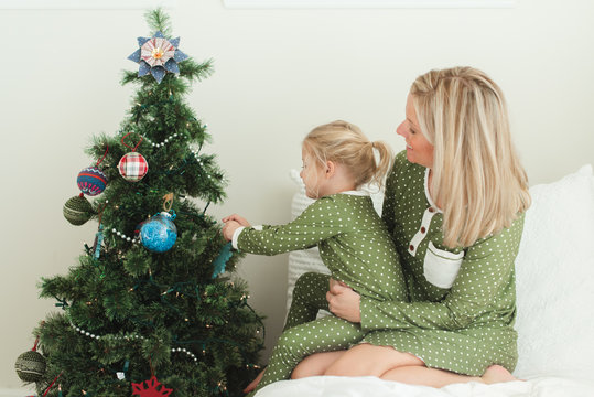 Daughter sitting on mother's lap while decorating Christmas tree