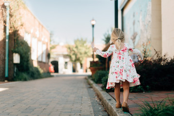 Young girl in a floral dress balancing on the edge of a sidewalk