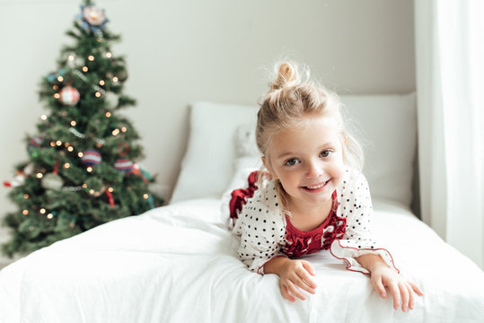 Smiling young girl lying on a bed