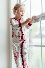Young girl standing on a window sill looking outside