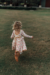 Young girl in a floral dress walking along the grass