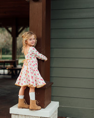 Young girl holding onto a column of a building