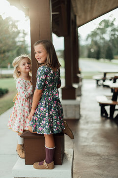 Two young girls holding onto a column of a building