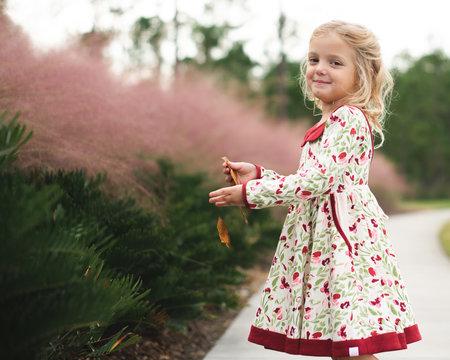 Smiling girl holding a leaf
