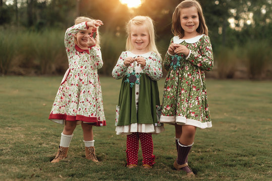 Three young girls holding Christmas ornaments