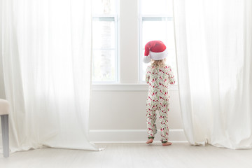 Young girl looking out of the window wearing a Santa hat