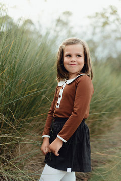 Young girl posing near a field of grass