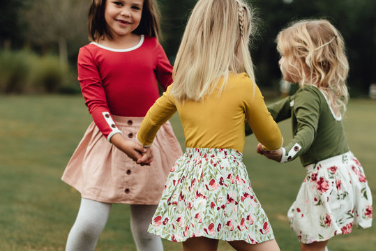 Young girls holding hands and playing