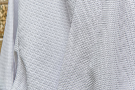 White bathrobes for home and hotel. Bathrobe waffle. Bathrobe suede gently cream color. Warm and soft textiles. Dressing gowns from high-quality cotton. Bathrobe for men on a hanger in the bathroom.