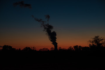 a nuclear power plant's cooling tower at sunset